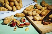 Peanuts on cutting board, on wooden background