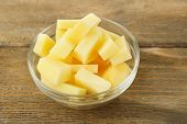 Raw peeled and chopped potatoes in glass bowl  on wooden background