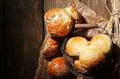 Tasty buns with sesame in  basket, on wooden background