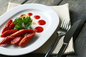 Smoked thin sausages and vegetables on plate, on wooden background
