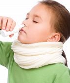 image of snot  - Cute girl spraying her nose with nasal spray isolated over white - JPG
