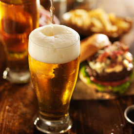 stock photo of cold drink  - ice cold beer pouring into glass with burgers at restaurant table - JPG