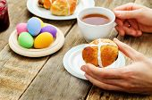 Easter Breakfast. Man Holding The Bun With A Cross And A Cup Of Tea.