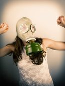 image of rubber mask  - Woman wearing gas mask with hands up - JPG