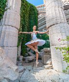 dancer stands on tiptoes, ballet pirouette. Outdoors, spring