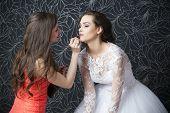 foto of makeup artist  - Makeup artist applies lipstick bride - JPG