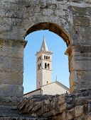 Bell tower of St. Anthony Church in Pula Croatia seen through the arc of Amphitheater