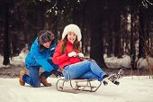 foto of sled  - Positive couple sledding in winter park on Valentine - JPG