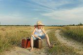 Teenage Traveler Waiting And Sitting On Luggage
