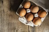 stock photo of low-light  - Fresh eggs in egg box in moody natural lighting vintage style set up - JPG