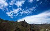 stock photo of wispy  - Gran Canaria February wispy cirrus clouds over Roque Bentayga - JPG
