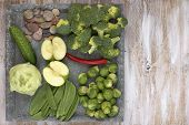 Set of vegetables on white painted plate and wooden background.