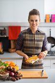 Portrait Of Happy Young Housewife Peeling Corn