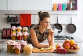 Young Housewife Standing Near Jars With Fruits Jam And Eating Ap