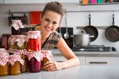 stock photo of pickled vegetables  - Portrait of happy young housewife looking out from jars with homemade fruits jam and pickled vegetables - JPG