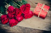 Roses And Gift Box On Wooden Background