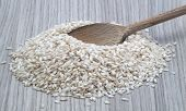 White raw rice and wooden spoon