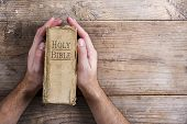 foto of holy-bible  - Hands holding Bible on a wooden desk background - JPG