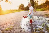 image of children walking  - Little boy playing outside in a puddle - JPG