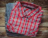 Plaid Shirt And Pair Of Jeans On Wooden Background. Top View. Vintage Stylized.