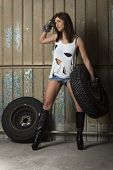 stock photo of cleavage  - woman in sexy clothing and tires in the garage - JPG