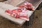 foto of slaughter  - Pieces of pig over wooden trough - JPG