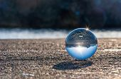 stock photo of crystal glass  - Glass transparent ball on dark background and grainy surface - JPG
