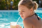 Little Blond Girl Drinks Fruit Cocktail Through Plastic Tube