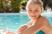 Smiling Little Blond Girl With Cocktail In Swimming Pool
