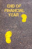 Yellow Footsteps On Sidewalk Towards End Of Financial Year Message