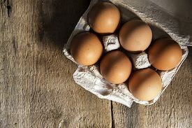 picture of nest-egg  - Fresh eggs in egg box in moody natural lighting vintage style set up - JPG