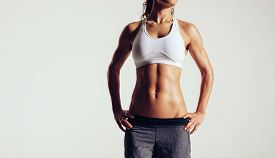 picture of sportswear  - Cropped image of muscular young woman posing in sportswear against grey background - JPG