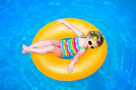 stock photo of floating  - Cute funny little toddler girl in a colorful swimming suit and sun glasses relaxing on an inflatable toy ring floating in a pool having fun during summer vacation in a tropical resort - JPG