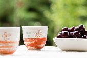foto of teapot  - fresh healthy hot tea in a teapot and cup whit cherries - JPG