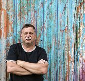 stock photo of 55-60 years old  - Mature mustachioed man sitting against the wall - JPG