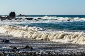 stock photo of atlantic ocean  - Waves and foam on wild stone beach on shore of the Atlantic ocean with sky and rock on skyline or horizon in Tenerife Canary island Spain at spring or summer - JPG
