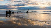 picture of shipwreck  - a shipwreck on the beach with cloud reflections off the wet sand - JPG