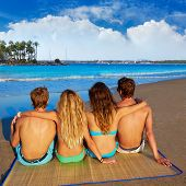 picture of couple sitting beach  - friends group couples sitting in beach sand rear view Alcudia Mallorca photo mount - JPG