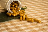 image of pharmaceuticals  - Medicine bottles plastics pharmaceuticals medicine capsule cotton texture background leaves herbs herbal products. ** Note: Shallow depth of field - JPG