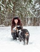picture of dog ears  - Happy girl smiling and holding a mountain dog behind the ears - JPG