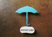 picture of medicare  - A paper umbrella over a Medicare message - JPG
