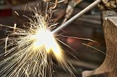 stock photo of torches  - A metal fabricator utilizing a torch to heat up a piece of metal in order to shape it - JPG