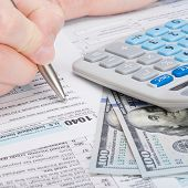 picture of cpa  - Taxpayer filling out USA 1040 Tax Form  - JPG