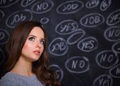 stock photo of yes  - Thinking young woman with yes or no choice on grey background - JPG