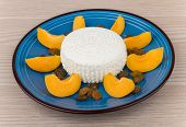 picture of curd  - Grainy curd with raisins and slices of peach in blue glass plate on table - JPG