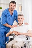 image of male nurses  - Kind male nurse and his senior patient in wheelchair at hospital - JPG