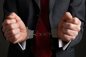 pic of handcuff  - Close Up Of Businessman Wearing Handcuffs Illustrating Corporate Crime - JPG