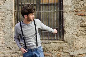 foto of suspenders  - Portrait of young man wearing suspenders in urban background - JPG