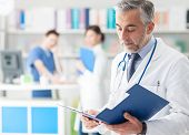Confident Doctor Checking Medical Records poster