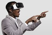 Surprised African Businessman Using Oculus Rift Headset, Experiencing Virtual Reality While Playing poster